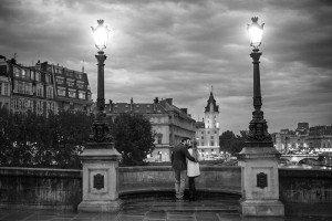 Romantic photo of couple on Paris bridge at dusk, photo by TripShooter's photographer in Paris, Christian Perona