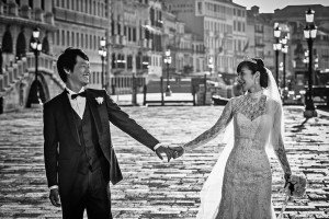 Wedding in Venice - bride and groom hod hands in street - by TripShooter's Venice photographer Matteo Michelino