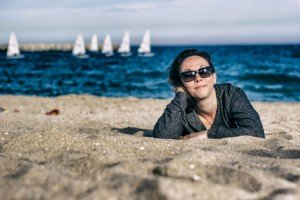 Travel portrait of woman on coast lying on beach, by TripShooter's Budapest photographer Oliver Sin