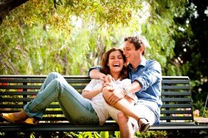 Travel portrait of happy couple laughing on park bench by TripShooter's Barcelona photographer Pablo Romero