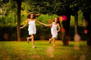 Sisters run through park holding hands, by TripShooter's Barcelona photographer Pablo Romero
